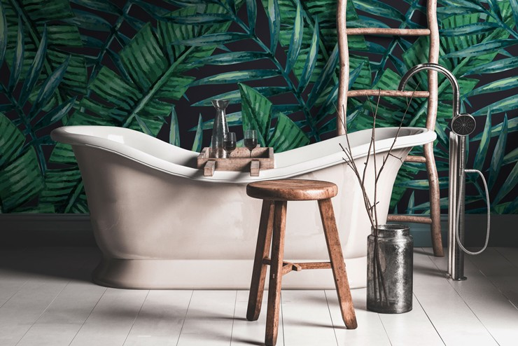 painted dark jungle leaves wallpaper in boho style bathroom with free-standing tub and wooden stool