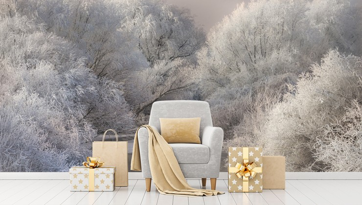 grey armchair with gold cushion and golden wrapped presents with snowy forest wallpaper
