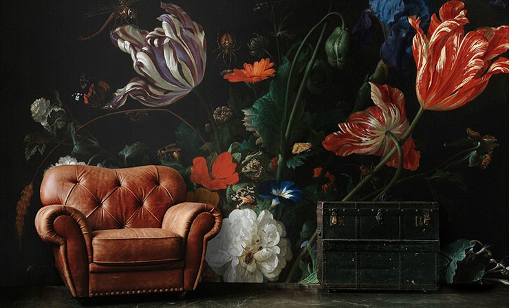 antique painted flowers wall mural with brown leather chair and black chest
