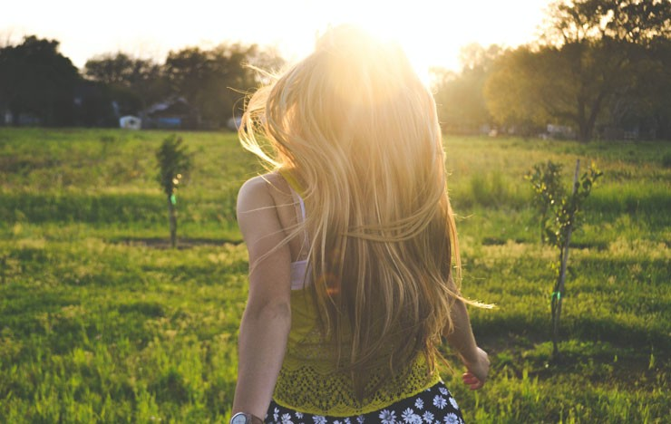 blonde lady running in a sunset lit meadow