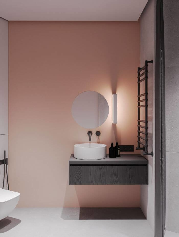 pink minimalist bathroom design with round mirror and grey accessories