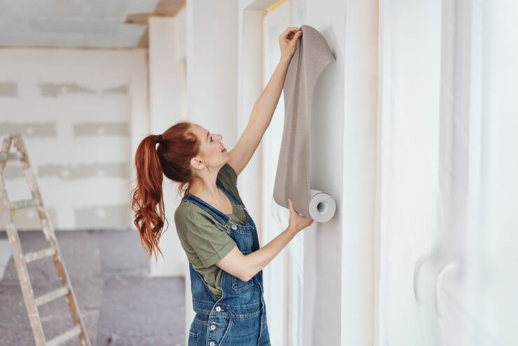 red haired woman pulling out brown wallpaper onto wall