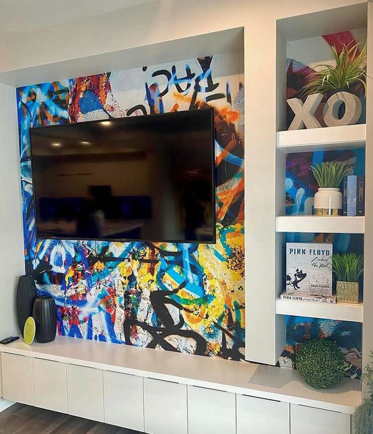 mounted tv and white shelving on colourful graffiti wallpaper