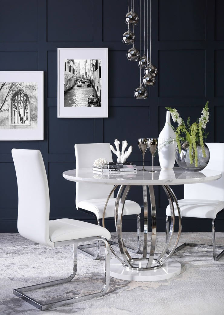 navy dining room with white dining chairs and table