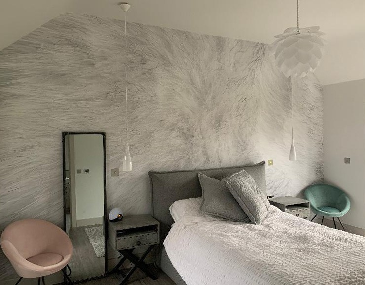 off-white/grey rabbit fur wallpaper in bedroom with pastel pink and green accessories