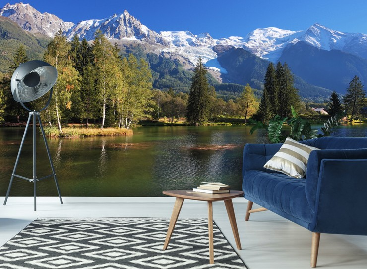 beautiful lake and green forest with snowy mountains wallpaper with blue sofa and metal lamp