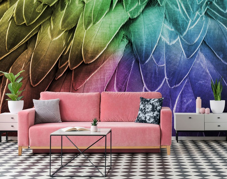 pink velvet sofa with black and white floor with rainbow feather wallpaper in background