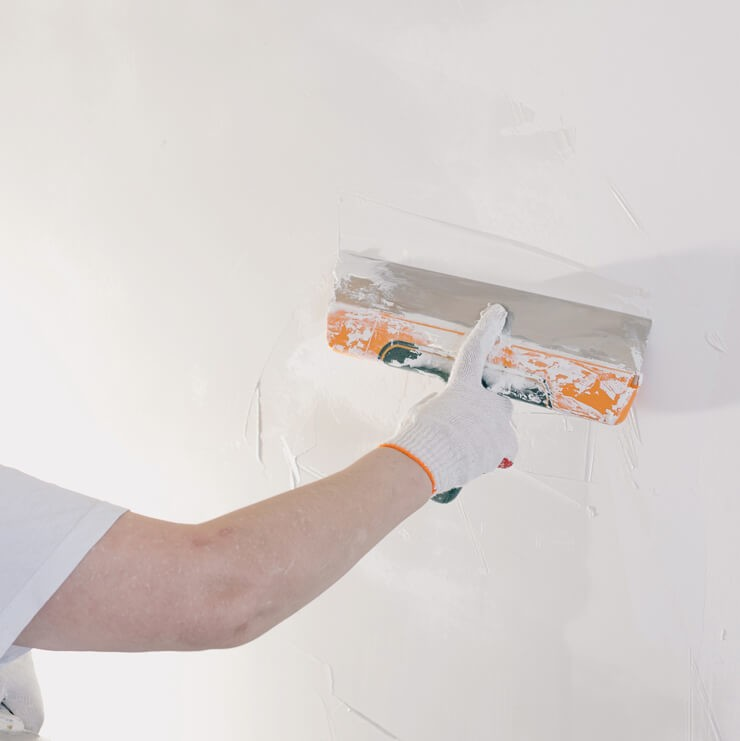 a glove hand plastering wall with white plaster