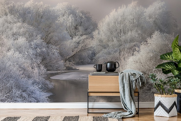 frosty forest with river running through wall mural in cosy lounge
