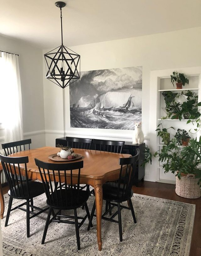 black and white painting of stormy sea with ship in minimalist trendy dining room