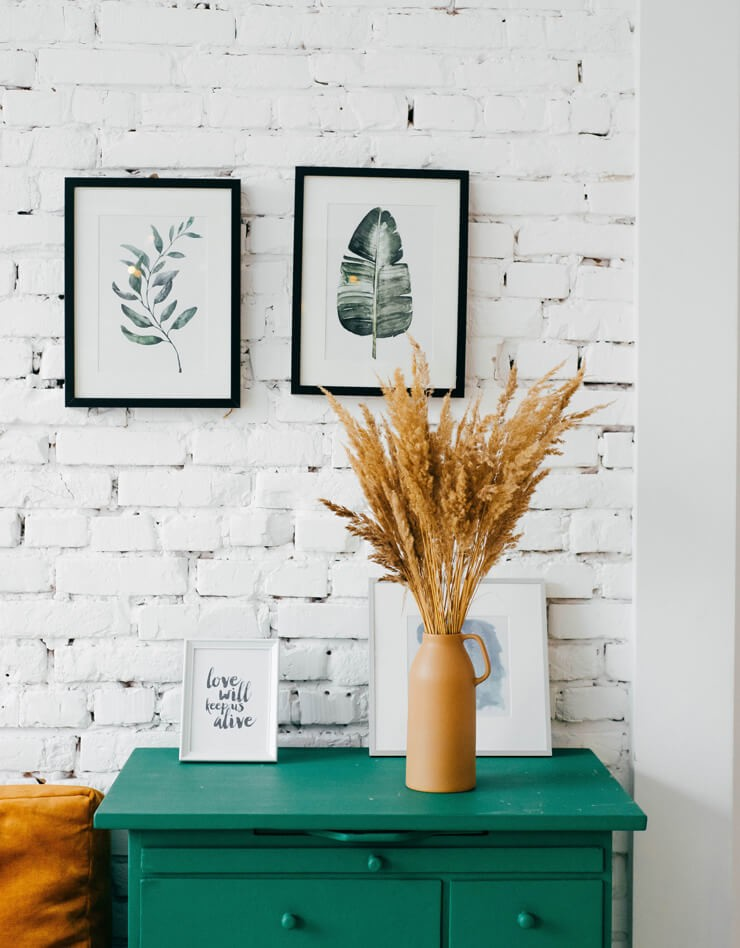 framed leaf prints inblack frames on white brick wall with orange vase and green drawers