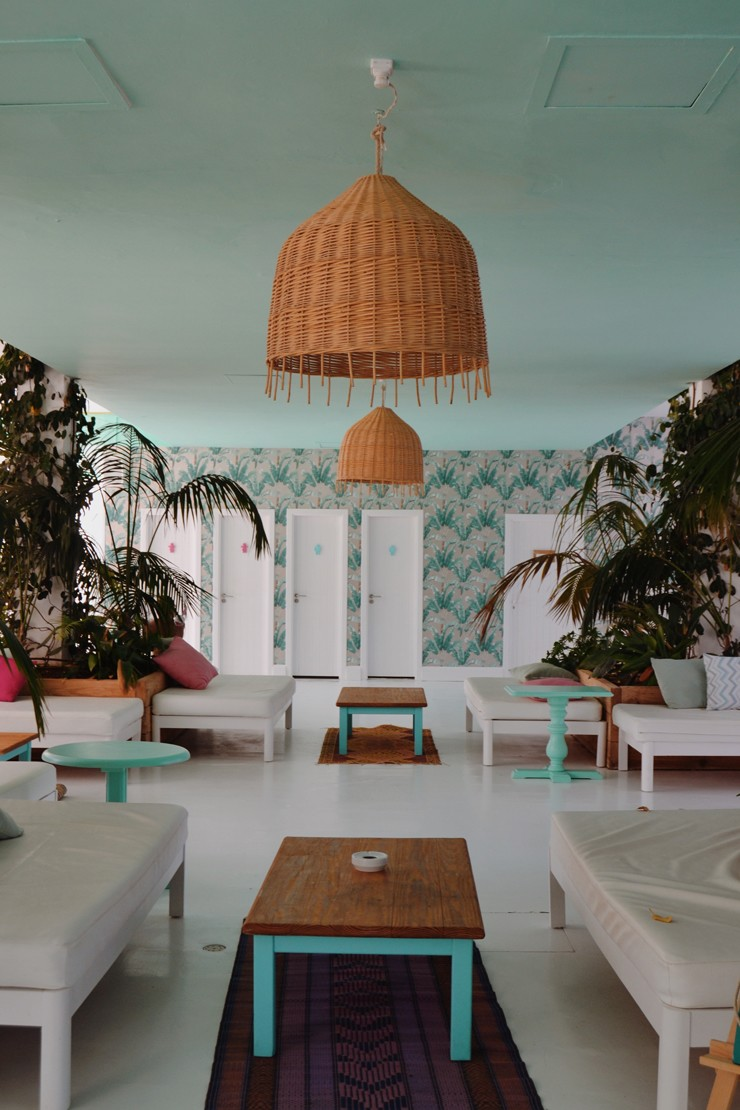 beach house room with wicker lampshades, duck egg blue ceiling and tropical wallpaper