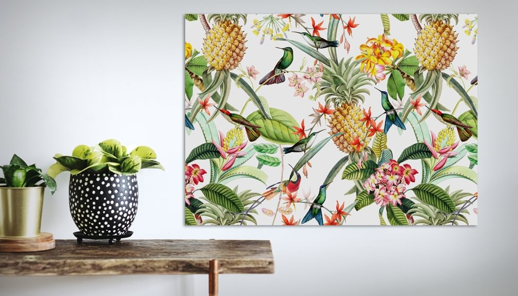 tropical pineapple and bird metal print in room next to wooden shelf